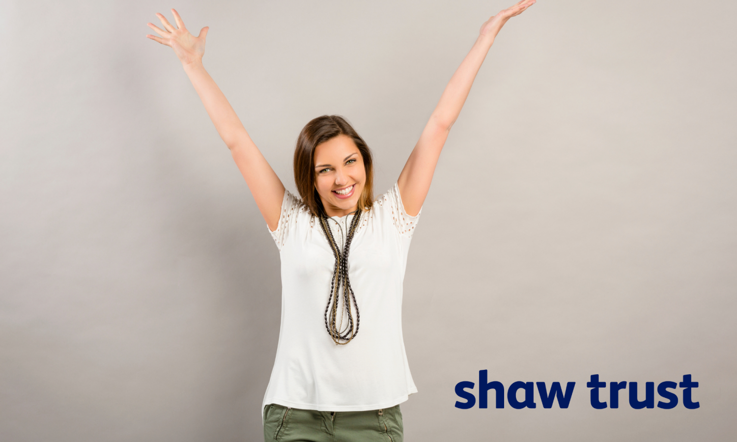Photo of a happy and confident woman with her hands in the air. Shaw Trust logo in the bottom right.