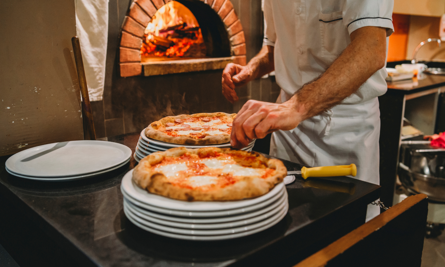 Photo of a pizza chef preparing two pizzas to put in the oven behind.